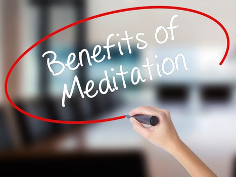 Woman Hand Writing Benefits of Meditation with a marker over transparent board. Isolated on Office. Business concept. Stock Photo