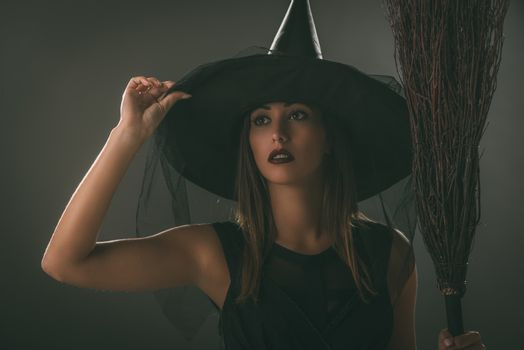Portrait of a young woman dressed like a witch. She is in dark clothing and holding a broom.