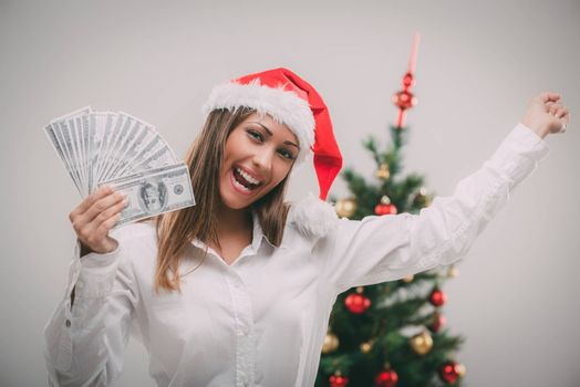 Successful businesswoman wearing santa hat and holding money. Looking at camera.
