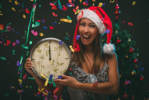Cheerful beautiful woman celebrating New Year and showing midnight on the clock. She is having fun, confetti is the air. Looking at camera.