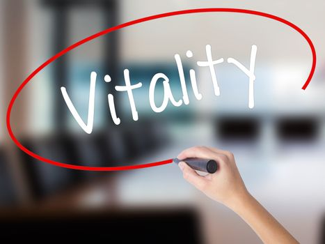 Woman Hand Writing Vitality  with a marker over transparent board. Isolated on Office. Business concept. Stock Photo