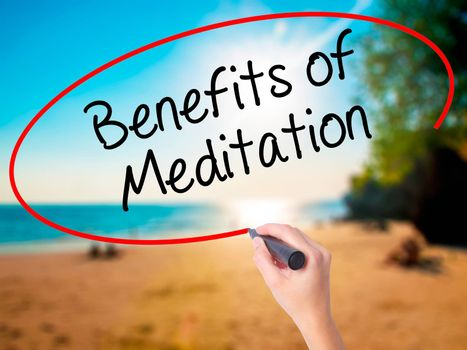 Women Hand writing Benefits of Meditation with black marker on visual screen. Isolated on beach. Business, technology, internet concept. Stock Photo