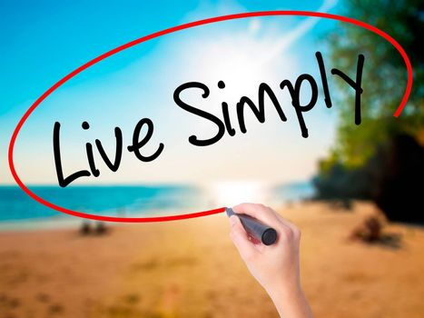 Women Hand writing Live Simply with black marker on visual screen. Isolated on beach. Business, technology, internet concept. Stock Photo
