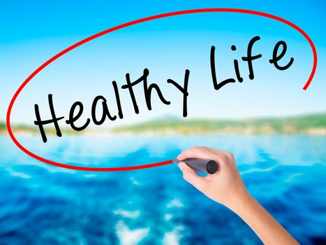 Woman Hand Writing Healthy Life black marker on visual screen. Isolated on white. Life, technology, internet concept. Stock Image