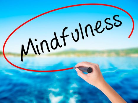Woman Hand Writing Mindfulness  on blank transparent board with a marker isolated over water background. Business concept. Stock Photo