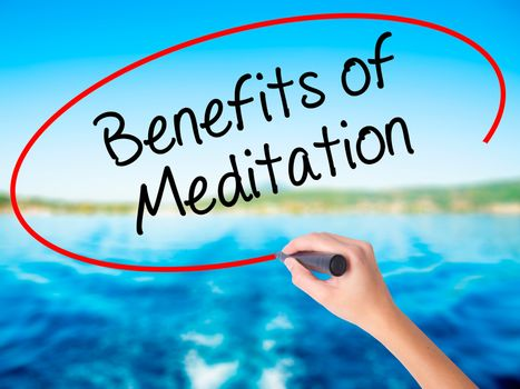 Woman Hand Writing Benefits of Meditation on blank transparent board with a marker isolated over water background. Business concept. Stock Photo