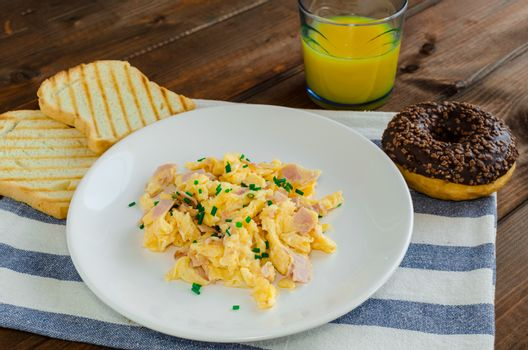 Scrambled eggs with toast and donut