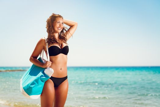 Portrait of a beautiful young woman enjoying on the beach. She is holding summer bag and looking away with smiling on her face.
