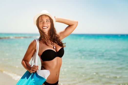 Portrait of a beautiful young woman with summer hat enjoying on the beach. She is holding bag and looking away with smiling on her face.
