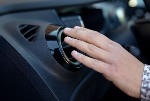 Driver hand on air ventilation grille with power regulator, modern car interior detail