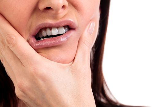Closeup of woman in strong toothache pain with hands over face. Dental health and care concept. Isolated on white background.