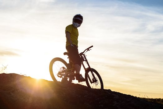 Silhouette of Cyclist in Helmet Standing with Mountain Bike on Rock at Sunset. Extreme Sport Concept.