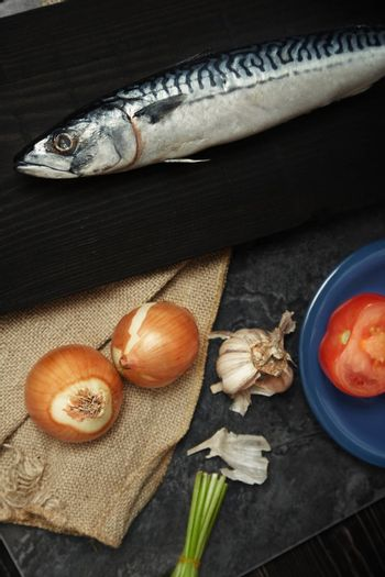 Mackerel and vegetables on a wooden table. Vertical photo