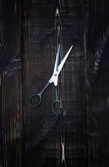Scissors on a wooden table background