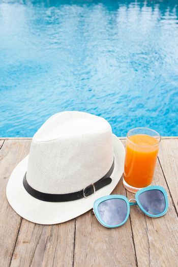 Summertime orange juice hat and sunglasses relax near swimming pool.