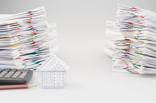 House with pencil and calculator with dual pile overload document