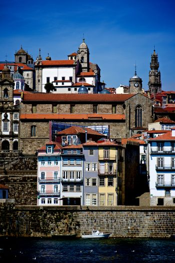 Cityscape of Old Town Porto with Traditional Portuguese Houses and View of Clerigos Tower against Blue Sky Outdoors