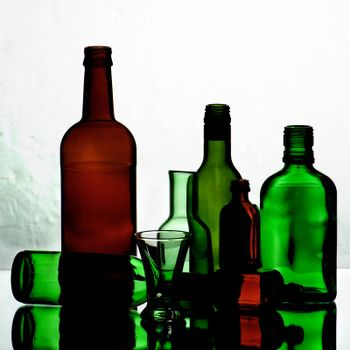 Arrangement of Various Empty Wine Colored Bottles and Glasses with Reflection on Mirror and Shadow Toned Backlight