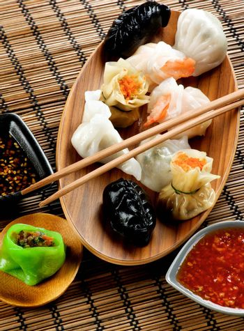 Various Dim Sum on Wooden Plate, Red Chili and Soy Sauces and Chopsticks closeup on Straw Mat background