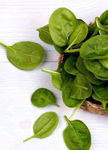 Small Raw Spinach Leafs in Wicker Plate Cross Section on Light Wooden background