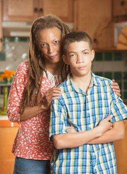 Disagreeable teen boy stands grimacing beside his loving mother