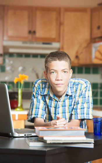 Calm attractive male teen leaning on kitchen counter with textbooks and laptop computer