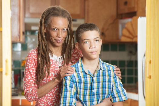 African-American mother and her frustrated teenaged son stand together in kitchen