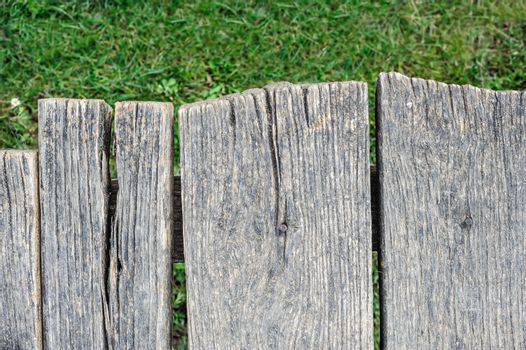 Edge of old aged cracked wood planks and green grass, natural organic background, top view
