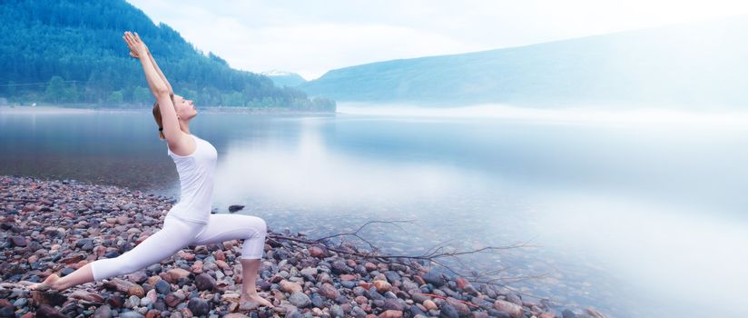 Young woman practice yoga on beach of foggy morning fjord in Norway
