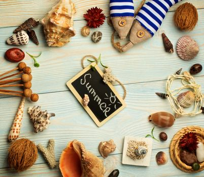 Summer Vacations Concept with Various Shells, Dry Plants, Handmade Decorations and Chalk Board with Inscription Summer closeup on Light Blue Wooden background. Retro Styled