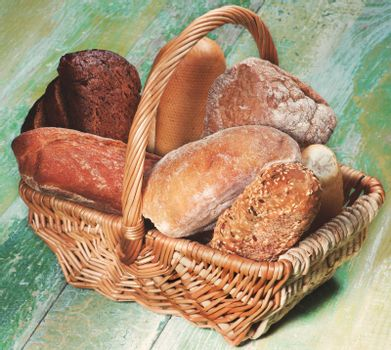 Various Buns, Baguette, Rye and Whole Wheat Bread in Wicker Basket closeup on Green Wooden background