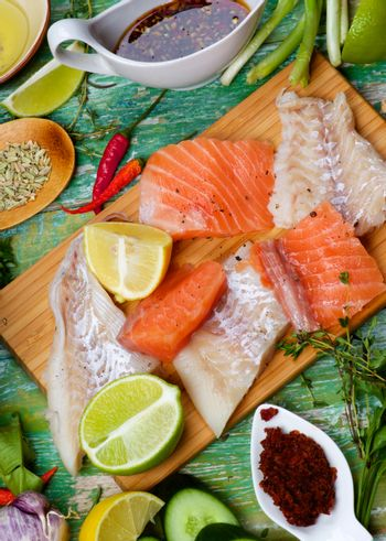 Food Background of Raw Thai Fish Cakes Ingredients with Vegetables, Spices, Herbs, Fruits, Prawns and Delicious Fillet of Salmon and Cod closeup on Cracked Wooden background