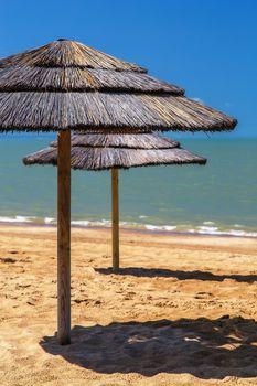 straw beach umbrella with blue sky