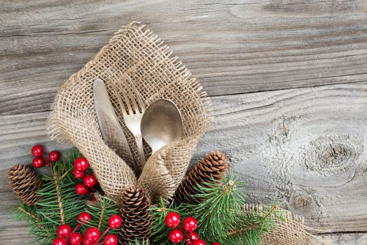 Christmas table with Christmas decoration: old knife, spoon and fork lie on the sacking napkin, as well as red holly berries and green spruce branch, which is located on an old wooden table, with space for text