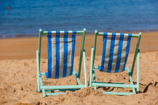Two empty deckchairs facing the sea