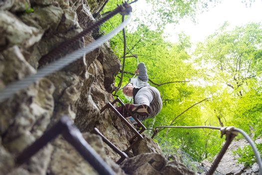 Woman climbing on the rocky route up the mountain.