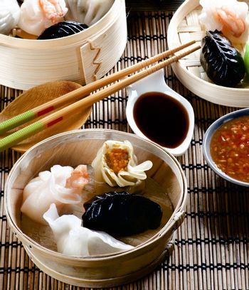 Assorted Dim Sum in Bamboo Steamed Bowls, Red Chili and Soy Sauces with Chopsticks closeup on Straw Mat background