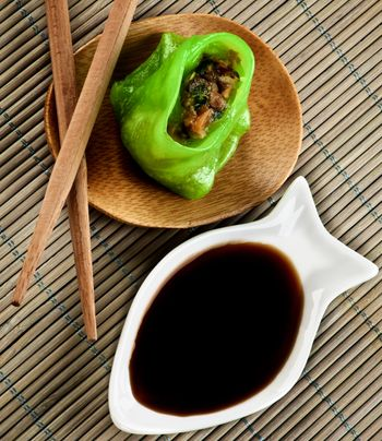 Vegetarian Yasai Dim Sum on Wooden Plate with Soy Sauce and Chopsticks closeup on Straw Mat background