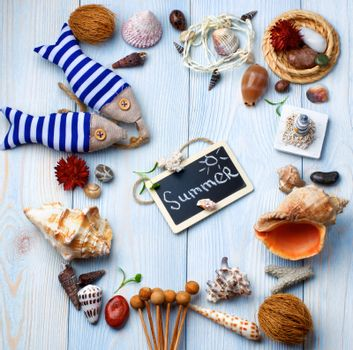 Summer Vacations Concept with Handmade Decorations, Various Shells, Dry Plants  and Chalk Board with Inscription Summer closeup on Light Blue Wooden background