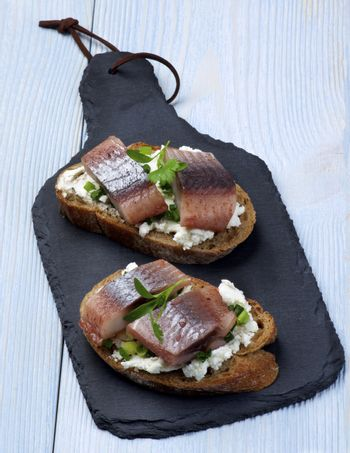 Delicious Sandwiches with Marinated Herring, Cream Cheese and Chives on Slices of Brown Bread closeup on Slate Board on Wooden background