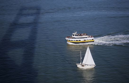 A ferry and sail boat cruising under the Golden Gate Bridge in San Francisco Bay.