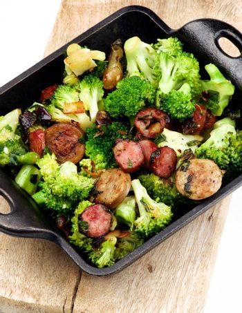 Homemade Stew with Broccoli and Grilled Sausages in Black Iron Cast on Wooden Board isolated on White background