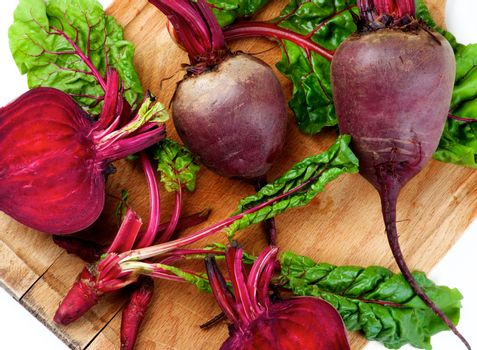 Arrangement of Fresh Raw Organic Beet Roots Full Body, Halves and Young Sprouts with Green Beet Tops closeup on Wooden Cutting Board. Top View