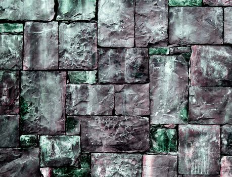 Background of Multi-Colored Cobblestones with Sharp Spears closeup Outdoors. Green and Gray Toned