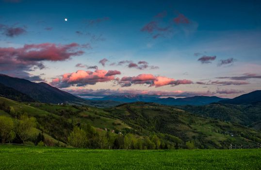 countryside landscape in mountains at dusk with moonrise. grassy meadow on a hillside behind the fence. spectacular evening sky with red clouds and moon