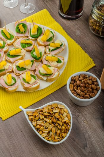 New Year's Eve meal - canapes with ham, cheese and spinach leaves, spicy cheese balls (Aigrettes), onion rings, roasted nuts with thyme and olive oil and beverages