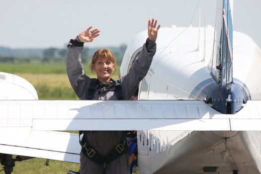 Aged woman waving to family before her first skydive