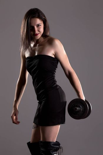 Sexy girl in short black dress, posing and lifting weights