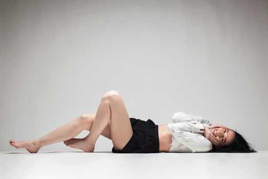 full body shot of beautiful black haired lady lying on the ground bare feet