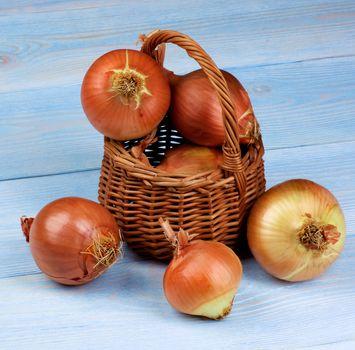 Wicker Basket Full of Ripe Raw Golden Onions on Blue Wooden background